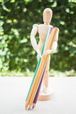 Wooden manikin carrying colour pencil on artist work table Stock Photography