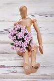 Wooden manikin with flowers. Stock Photo