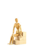 Wooden manikin sitting on blocks Royalty Free Stock Photo