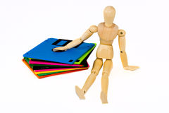 Wooden manikin sitting near diskettes Stock Images