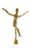 Wooden mannequin balancing over coins. Wooden manikin standing on one leg on coins royalty free stock photos