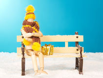 Wooden mannequin on a bench. Wooden mannequin with gift on a bench royalty free stock photos