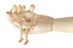 Wooden mannequin in big hand isolated Royalty Free Stock Photography