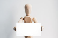 Wooden mannequin with a business card. Wooden mannequin holding a business card. Isolated white background Royalty Free Stock Photo