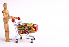 Wooden man with colorful candies in shopping trolley. Wooden mannequin buying sweets, white background, copy space stock photos