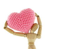 Wooden mannequin carry heart knit with yarn on the shoulder. White background Royalty Free Stock Photo