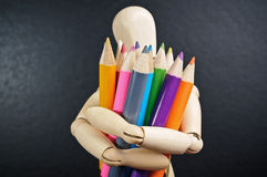 Wooden mannequin and color pencils Royalty Free Stock Photography