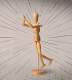 Wooden mannequin concept. Wooden mannequin posed in front of a greyish background with black lines around him royalty free stock photos