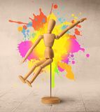 Wooden mannequin concept. Wooden mannequin posed in front of a greyish background with colorful splashes behind it royalty free stock photo