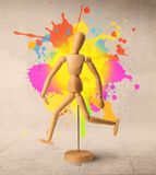 Wooden mannequin concept. Wooden mannequin posed in front of a greyish background with colorful splashes behind it stock image