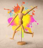 Wooden mannequin concept. Wooden mannequin posed in front of a greyish background with colorful splashes behind it stock images