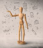 Wooden mannequin concept. Wooden mannequin posed in front of a greyish background with hobby related scribbles behind it stock images