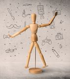 Wooden mannequin concept. Wooden mannequin posed in front of a greyish background with hobby related scribbles behind it royalty free stock photo