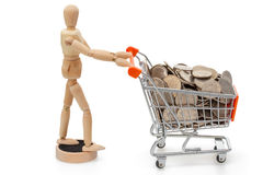 Wooden mannequin / doll with shopping trolley full of coins Stock Photography