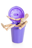 Wooden mannequin doll sitting in purple dustbin can, isolated Stock Images