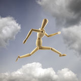 Wooden mannequin in the dramatic sky. Running and jumping concept.  stock photo