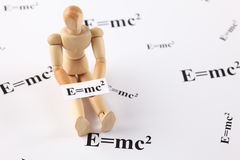 A wooden mannequin with formula E=mc2. A wooden mannequin holds a physical formula E=mc2 stock images