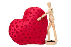 Wooden mannequin with a gigantic soft red heart Royalty Free Stock Images