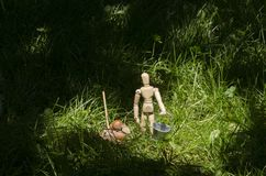 Wooden mannequin in green grass with miniature bucket and shovel stock photo