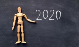 Wooden mannequin with handwriting text on chalk board. 2020 concept. Wooden mannequin with handwriting text on chalk board, panorama, copy space royalty free stock photography