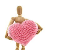 Wooden mannequin holding heart knit with yarn. On white background royalty free stock images
