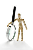 Wooden mannequin holding magnifying glass Stock Photos