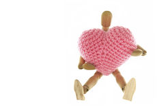 Wooden mannequin hugging heart knit with yarn. Isolated on white background stock image