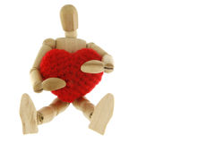 Wooden mannequin hugging heart knit with yarn. Isolated on white background Stock Photos