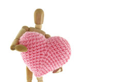 Wooden mannequin hugging heart knit with yarn. On white background Stock Photos