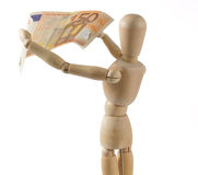 Wooden Mannequin Inspecting a Banknote stock photography
