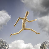 Wooden mannequin is jumping over the abyss at cloudy sky background. Big jump concept stock photo