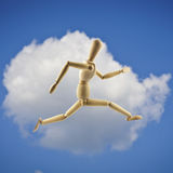 Wooden mannequin jumping or running. White cloud and blue sky as. Wooden mannequin jumping or running in the blue sky. White cloud and blue sky as background royalty free stock photo