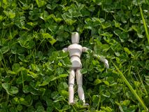 Wooden mannequin lying down on clover on springtime Ecology and garden concept. Wooden mannequin lying down on clover on springtime Ecology concept stock photography
