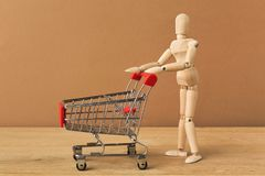Wooden mannequin with miniature shopping cart. Wooden mannequin with miniature toy empty shopping cart on brown background, business, shopping concept. Mockup stock images