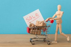 Wooden mannequin with miniature shopping cart. Wooden mannequin with miniature toy shopping cart with gifts on blue background, shopping concept. Mockup for stock photos