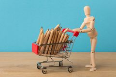 Wooden mannequin with miniature shopping cart. Wooden mannequin with miniature toy shopping cart with pencils on blue background, business, shopping concept stock photo