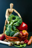 Wooden mannequin and a mix of vegetables and fruits Royalty Free Stock Photography