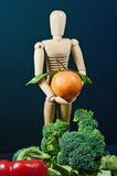Wooden mannequin and a mix of vegetables and fruits Royalty Free Stock Image