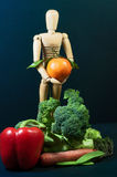 Wooden mannequin and a mix of vegetables and fruits Stock Photo