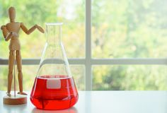 Wooden mannequin model with Erlenmeyer flask royalty free stock photos