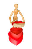 Wooden mannequin opens heart shaped gift box Royalty Free Stock Image