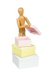 Wooden mannequin opens little box. Isolated on white stock photo