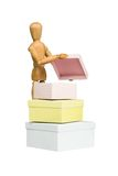 Wooden mannequin opens little box. Isolated on white stock photos