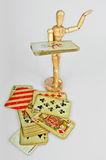 Wooden mannequin with playing cards. Wooden mannequin with old vintage poker cards royalty free stock images