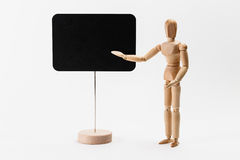 Wooden mannequin. Pointing on a canvas, as presenting something stock photos