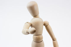 A wooden mannequin pointing at us. The upper body of a wooden mannequin pointing at us, in front of a white background stock image