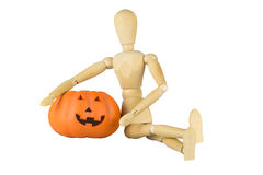 Wooden mannequin posing with a pumpkin royalty free stock image