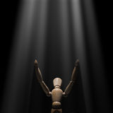 Wooden mannequin raised hands to light Royalty Free Stock Image
