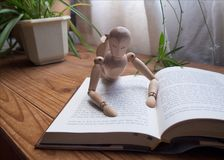 Wooden mannequin reading a book royalty free stock image