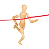Wooden mannequin running through finishing line Stock Photos